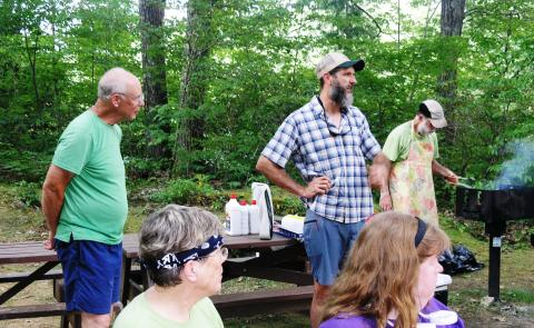 (Left to Right) Jim Pelletier, Past Chair of the MA Appalachian Trail Management Committee and Adam Brown, Appalachian Trail Conservancy Trails Resource Manager, New England; with Cosmo Catalano, Chair of the MA Appalachian Trail Management Committee in background heroically grilling on a very hot day